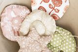 Steppanhänger: Für diese Softies zwei Stoffteile nach Vorlage ausschneiden, rechts auf rechts legen. 20 cm Zierband falten und als Schlaufe zum Aufhängen zwischen die Stoffe legen. Teile rundherum zusammensteppen, dabei eine Öffnung lassen. Wenden, mit Füllwatte ausstopfen und Öffnung schließen. Füllung verteilen, Zierkreis in der Mitte steppen.    Das braucht ihr: Bleistift, Schere, Stoffreste, Füllwatte, Geschenkbänder und eine Nähmaschine  Und so geht's: Kopiert die Vorlage auf das gewünschte Maß. Hier geht's zur Bastelvorlage für den Steppanhänger