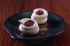 Nougat-Cups aus Baiser mit einer Füllung aus Zartbitter-Kouvertüre, Nougat und Blattgold. Wer mag, kann auch einfach Zuckerperlen oder Haselnüsse an Stelle des Blattgolds nehmen. Zum Rezept: Nougat-Cups