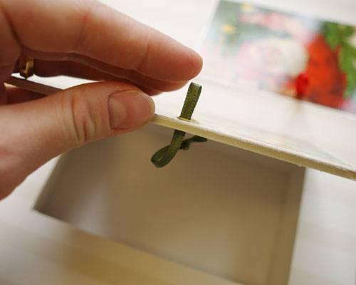 6.) Mit dem Cutter an den linken Rand der Karten mittig einen Schnitt setzen und ein Stück Satinband als Schlaufe hindurchziehen. Band auf der Innenseite verknoten, Tür wieder schließen.