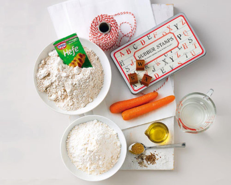 Zutaten für ein Möhrenbrot 300 g Dinkel-Vollkornmehl, 200 g Weizenmehl (Type 505), 1 Päckchen Trockenhefe, 1-2 TL Meersalz, je 1/2 TL Anissaat und frisch gemahlenen schwarzen Pfeffer, 200 g Möhren, Olivenöl, Salz für die Form Für die Verpackung: Brottüten aus Papier, Buchstabenstempel, Stempelkissen, Kordel
