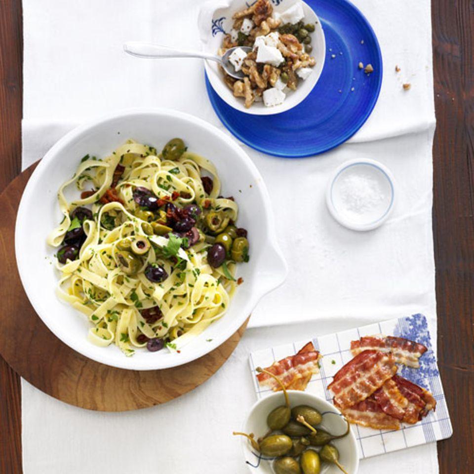 Das Grundrezept sind diesmal Bandnudeln mit Olivensoße. Dazu gibt's entweder gebratenen Bacon mit Kapernäpfeln oder - als vegetarische Alternative - eine Schafkäse-Nuss-Mischung. Wichtig, wenn Vegetarier und Fleisch-Fans an einem Tisch sitzen: Utensilien wie Töpfe oder Messer strikt trennen. Keine Vegetarierin mag Nüsse aus einer Pfanne, in der vorher Speck gebraten wurde. Zum Rezept: Bandnudeln mit Olivensoße