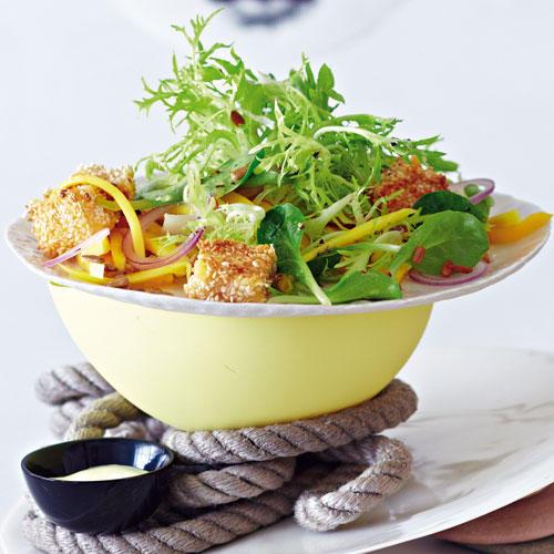 Gebratener Käse in Sesampanade auf grünem Salat mit Mango
