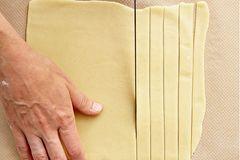 Alle 4 Teige übereinander gestapelt auf dem Backpapier für weitere 45 Minuten kalt stellen.    Eine helle und eine dunkle Teigplatte mit einem Messer in gleichmäßig dicke Streifen schneiden. Jeden zweiten hellen Teigstreifen zur Hälfte nach oben legen.