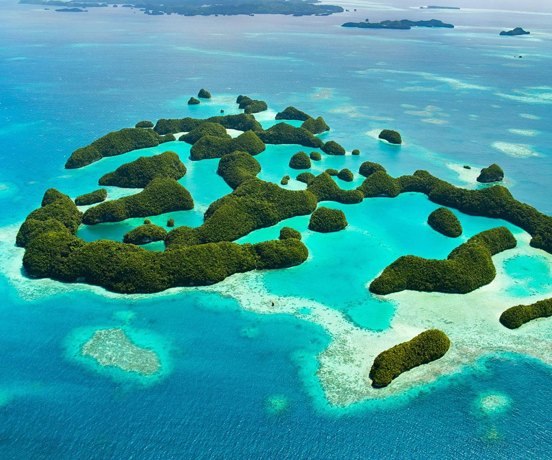"""Platz 4: Palau Wie bitte? Was für ein Land? Ja, Palau liegt im Pazifik und gilt als Länder-Zwerg. Warum sich eine Reise dennoch lohnt: """"Hinter einem 110 km breiten Barriereriff liegen 200 Atolle aus vulkanischen Gesteinen und Kalkstein – nur acht davon bewohnt –, die bedeckt sind von Mangroven und tropischen Wäldern und umgeben von Gewässern, in denen es nur so von tierischem Leben wimmelt. Konstante Temperaturen und Niederschläge, die dank ihrer Regelmäßigkeit gut einzuschätzen sind, machen Palau zum ganzjährigen Reiseziel, auch wenn es in der zweiten Jahreshälfte öfter Taifune gibt."""""""