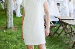 Gelungene Kombination: Zum schlichten weißen Minikleid und Haarband passen auch derbe braune Lederstiefel.