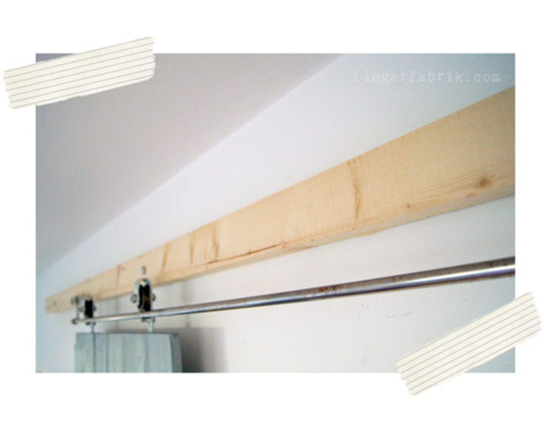 Zur Wandmontage habe ich einen langen Balken (6 x 8 cm) genommen und ihn mit massiven Schrauben in gewünschter Höhe an die Wand gedübelt. Die Rollen und die Laufschiene bekommt ihr in besagtem Geschäft.