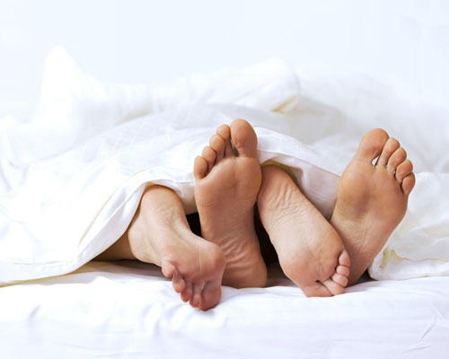 Paar Füße Bett