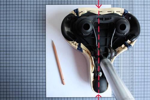 """Selbermachen: Falls Sie nicht das Universal-Schnittmuster verwenden, sondern einen maßgeschneiderten Fahradsattelbezug nähen wollen, gehen Sie so vor:     - lösen Sie den Sattel aus der Halterung    - nehmen Sie sich ein Din-A4-Blatt und zeichnen Sie parallel zur langen Seite mit dem Lineal eine Linie über die ganze Höhe des Blattes    - legen Sie nun den Sattel so auf das Blatt, dass die Linie oben und unten direkt auf der Hälfte des Sattels liegt (Achtung: perspektivisch bedingt ist beim Foto die rote Linie nach links verschoben. Tatsächlich liegt der Sattel aber direkt mittig auf der Bleistiftlinie)    - fahren Sie nun mit einem Bleistift um die Hälfte des Sattels, die auf dem Blatt liegt, und halten Sie den Bleistift dabei möglichst senkrecht    - nun nehmen Sie den Sattel weg, begradigen ein wenig Ihre """"Zitterstellen"""" und zeichnen Sie die Hälfte nochmal mit einem kräftigeren Strich nach"""