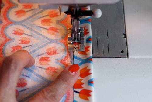 Selbermachen: Da Wachstuch nicht franst, können Sie den Seitenstreifen einfach mit Geradstich knappkantig (min. 1 cm vom Falz) einmal rundherum absteppen. Wachstuch kann man nicht mit Stecknadeln festheften, daher müssen Sie beim Nähen einfach ein bisschen festhalten. Notfalls können Sie die Kante auch mit Stylefix  fixieren.    Wachstuch näht sich leichter, wenn man einen Teflonfuß (auch Gleitfuß oder Antihaftfuß genannt) für die Nähmaschine hat. Diesen bekommen Sie für Ihr Modell im Nähmaschinen-Fachhandel oder online (z.B. unter www.naehpark.com). Muss man aber nicht.