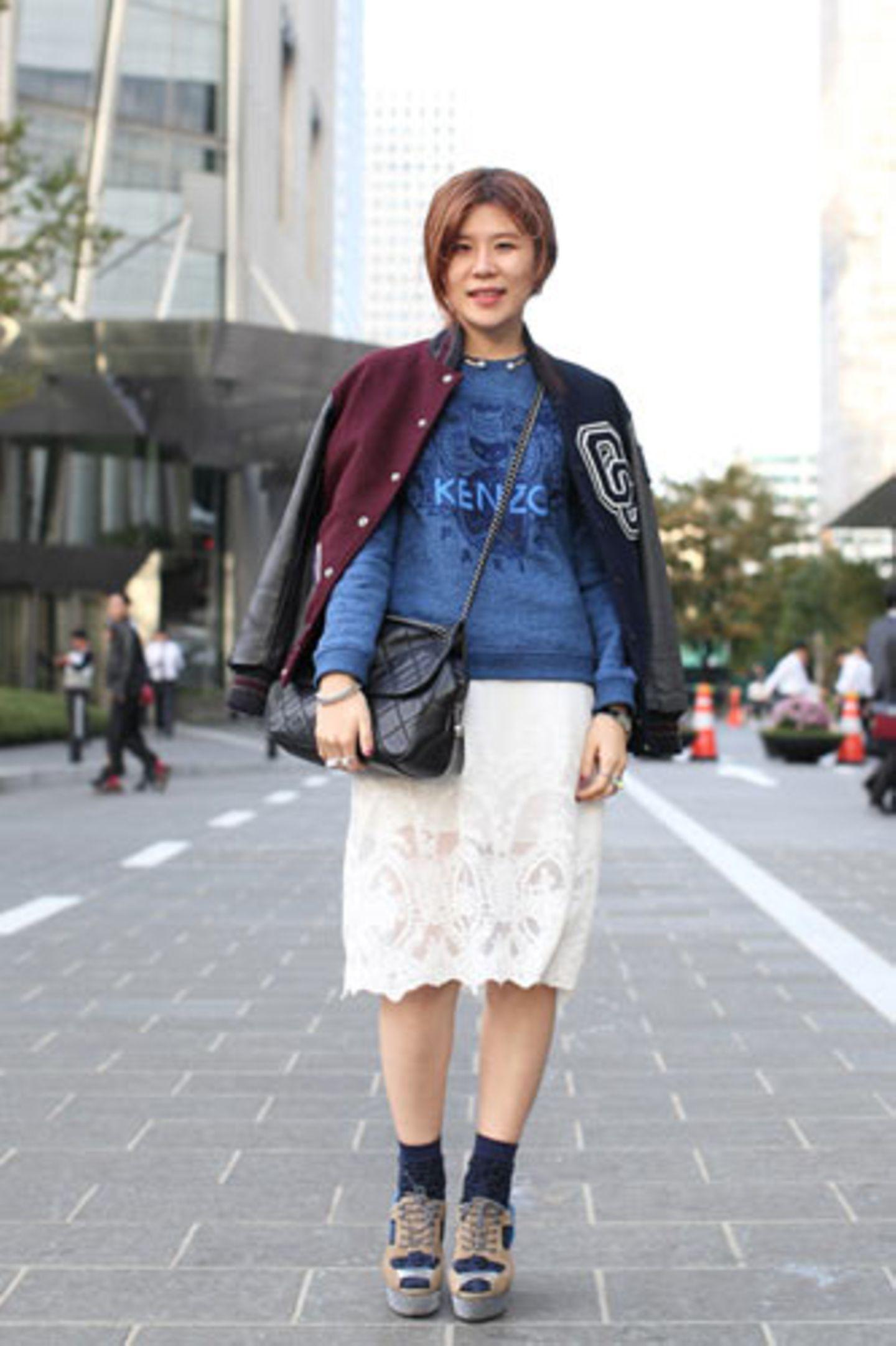 Die südkoreanische Bloggerin Stacey Young von StyleSophomore hat für uns stilsichere junge Damen auf den Straßen von Seoul fotografiert. Dabei fällt auf: Kenzo ist in Ostasien mindestens genauso beliebt wie bei uns. Zum Pulli mit dem typischem Schriftzug trägt Boram Seo einen Rock aus weißer Spitze, eine College-Jacke von Opening Ceremony und Schuhe von Opening Ceremony x Adidas. Mehr bei BRIGITTE Look der Woche: Stil aus Seoul zum Nachstylen Switcheroo: Wenn Paare ihre Kleider tauschen Streetstyle New York - Stil für Fortgeschrittene