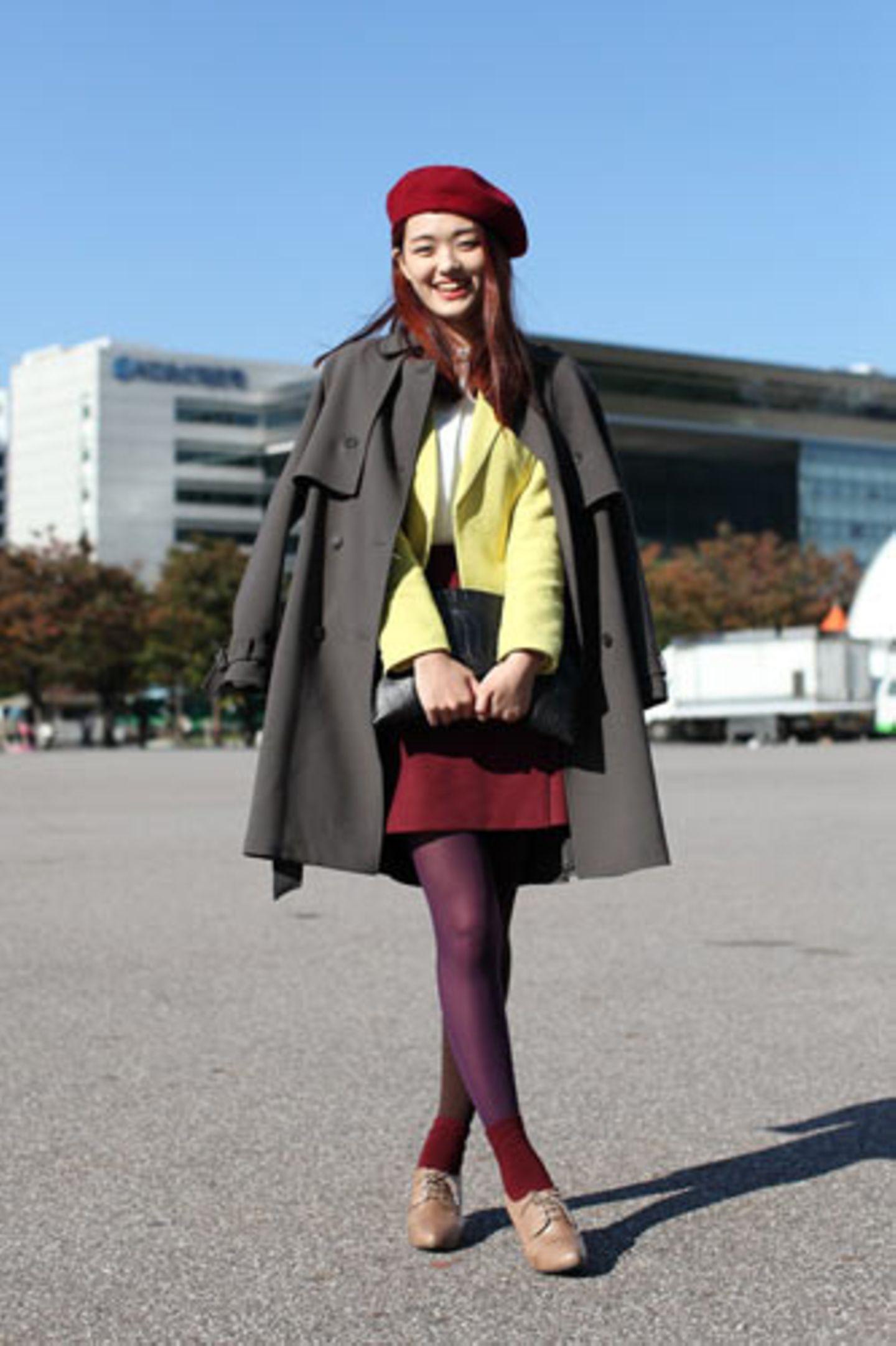 Beerentöne zu Gelb und Grau? Bei Park Hyejin ergibt das einen stimmungsvollen Farbmix. Ihr grauer Trenchcoat ist von Tomboy, der rote Rock von Tume, die brombeerfarbene Strumpfhose von Eight Seconds.