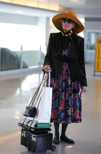 Modetrends aus Manhattan: Wir wissen leider nicht, wohin die Reise geht. Aber stilvoll ist die Dame mit ihrem bunten Kleid, dem großen Hut und dem kleinen Ziehköfferchen auf jeden Fall unterwegs.