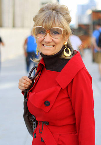 Modetrends aus Manhattan: Diese blonde New Yorkerin setzt auf Retro-Charme: Zum Mantel in der Trendfarbe Rot kombiniert sie einen schwarzen Rolli, goldene Ohrringe und eine überdimensionale 70er-Jahre-Brille. Wir finden: Die Zeitreise ist geglückt.