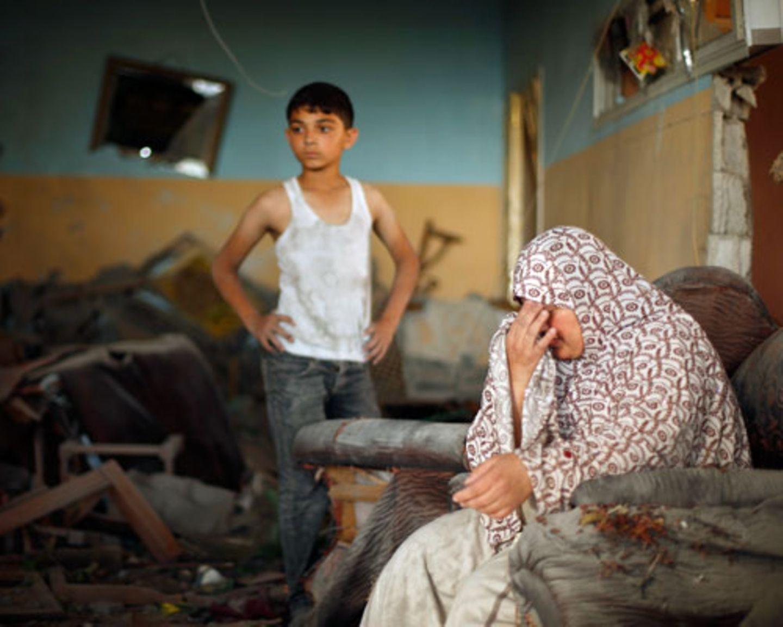 Ihr Leben ist in Trümmern. Eine Palästinenserin sitzt in ihrem Haus in Gaza-Stadt, das von einer israelischen Rakete zerstört wurde, und weint. Noch am Donnerstag hatte eine Waffenruhe für ein kurzes Aufatmen im Gaza-Streifen gesorgt. In den fünf Stunden, in denen nicht geschossen wurde, stürmten die Bewohner die Läden und Banken, um sich mit dem Nötigsten auszustatten. Kurz danach startete Israel die Bodenoffensive.
