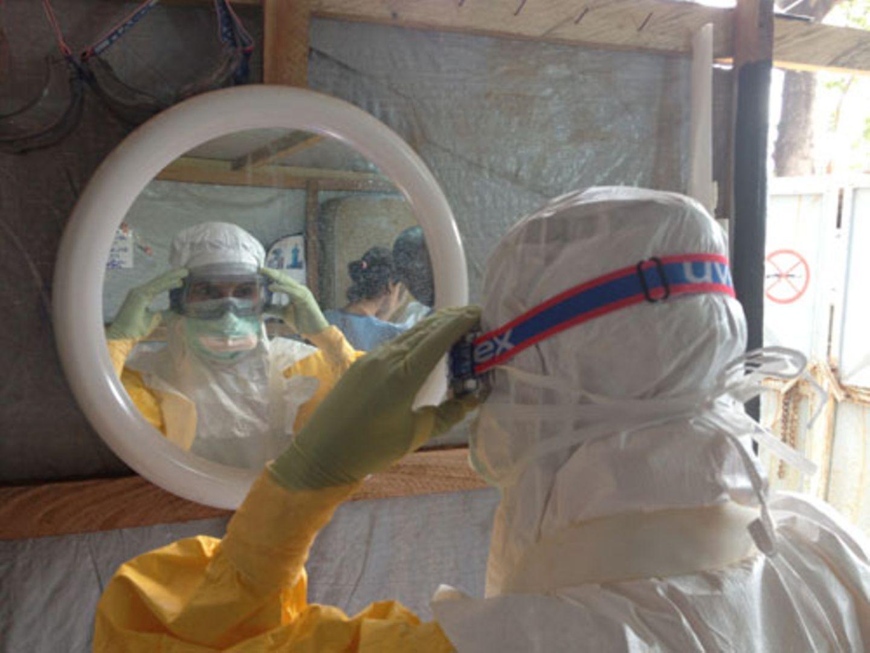 """Ebola ist eine der gefährlichsten und ansteckendsten Krankheiten weltweit. Mehr als 1000 Menschen haben sich in den westafrikanischen Ländern Guinea, Sierra Leone und Liberia infiziert, fast 700 von ihnen sind an der Krankheit gestorben. Auch zwei Ärzte haben sich Medienberichten zufolge bereits angesteckt. Es zeigt, wie wichtig Desinfektion und Schutzkleidung für die Helfer ist. Hier prüft eine Krankenschwester in einem Lager von """"Ärzte ohne Grenzen"""" in Guinea, ob Schutzbrille und Anzug richtig sitzen."""