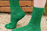 Lochmusterstreifen bilden ein Ypsilon vor geripptem Hintergrund: Um beim Stricken dieser Socken den Überblick zu behalten, sollten Sie Maschenmarkierer benutzen.    Sie möchten Thelonious nachstricken? Hier geht's zur Anleitung.