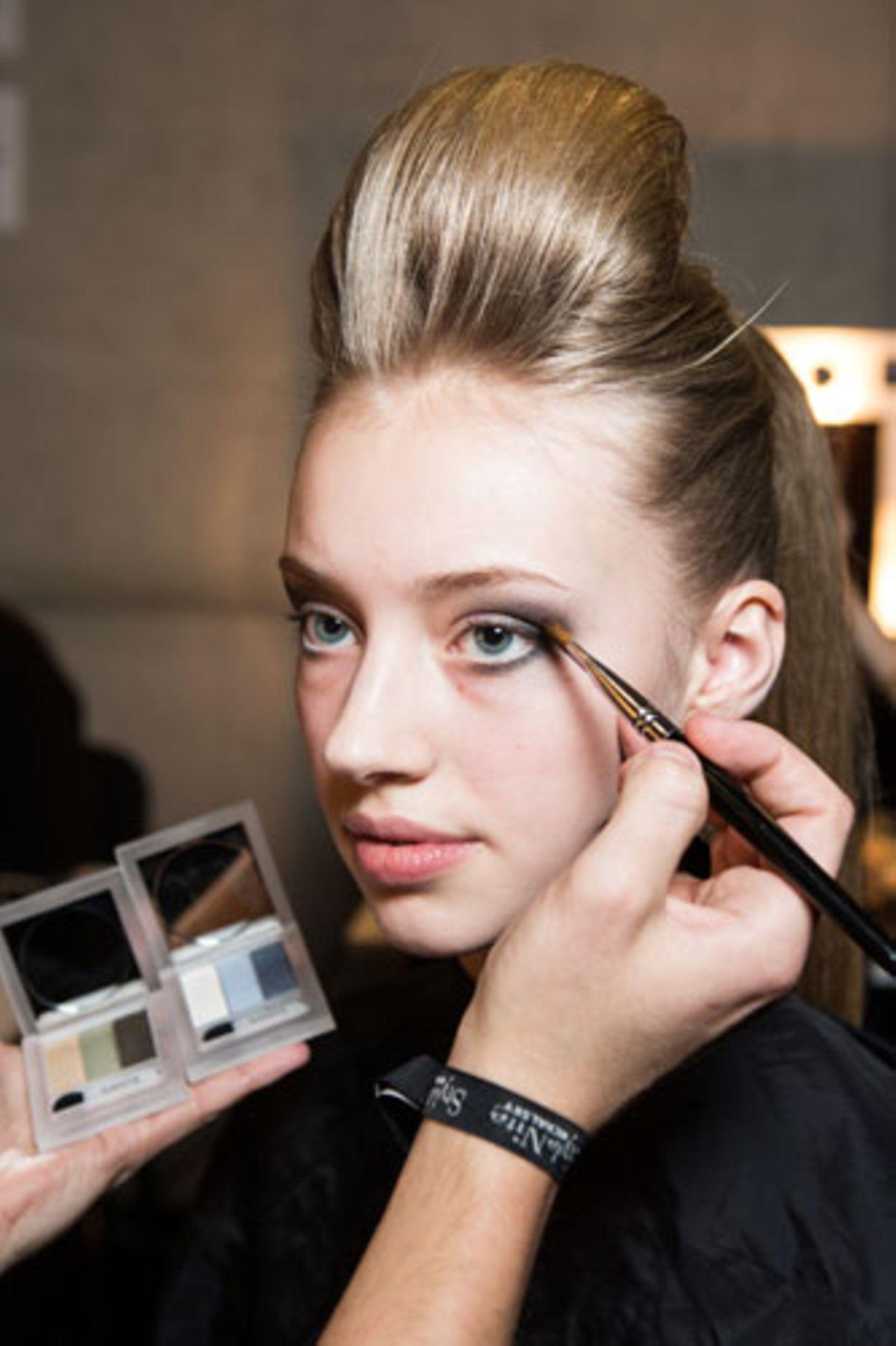 Mit einem flachen Pinsel wird der Lidschatten auch entlang des unteren Wimpernkranzes gesetzt und am äußeren Augenwinkel mit der Farbe vom oberen Lid verblendet.
