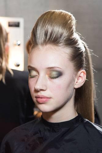 Fashion Week Berlin: Anschließend wird ein ein hellerer Grünton in die Mitte des Lids gesetzt. Im inneren Augenwinkel schminkt Benjamin Becher eine noch hellere Grünnuance. Dadurch wird das Auge optisch geöffnet.