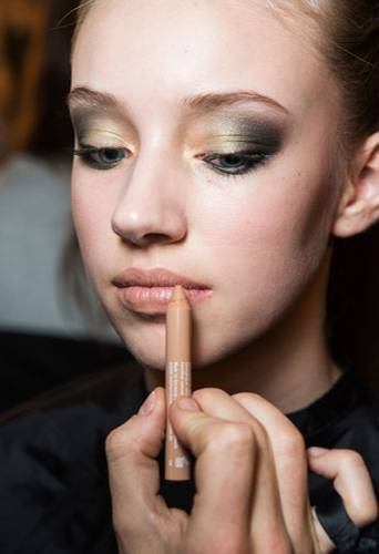 Fashion Week Berlin: Auch die Lippen sollen den Augen nicht die Schau stehlen. Hierfür setzt Benjamin Becher auf einen ganz speziellen Trick: Mit einem Abdeckstift, der normalerweise Rötungen kaschiert, malt er die Lippen leicht nach. Nude Lips mal anders!