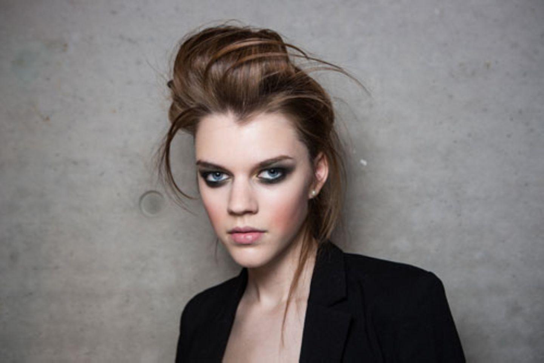 Der Fokus des Make-ups liegt ganz klar auf den Augen: Smokey Eyes mit grünen Nuancen, dazu Apfelbäckchen und Nude Lips.
