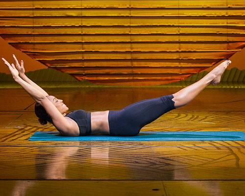 Workout: ...Beim Einatmen die Arme in einer fließenden Bewegung nach hinten nehmen und lang machen, gleichzeitig die Beine strecken. Der Körper bleibt dabei stabil und bildet ein weites V. Dann langsam die Beine in Kreisform anziehen, die Hände bewegen sich wieder zu den Außenseiten der Knie. Anschließend die Arme und Beine wieder strecken und die Übung von vorne anfangen. Die Beine und Arme berühren den Boden zu keiner Zeit. 5-mal wiederholen, dann kurz entspannen. Während der gesamten Übung gleichmäßig atmen. 2 weitere Durchgänge.