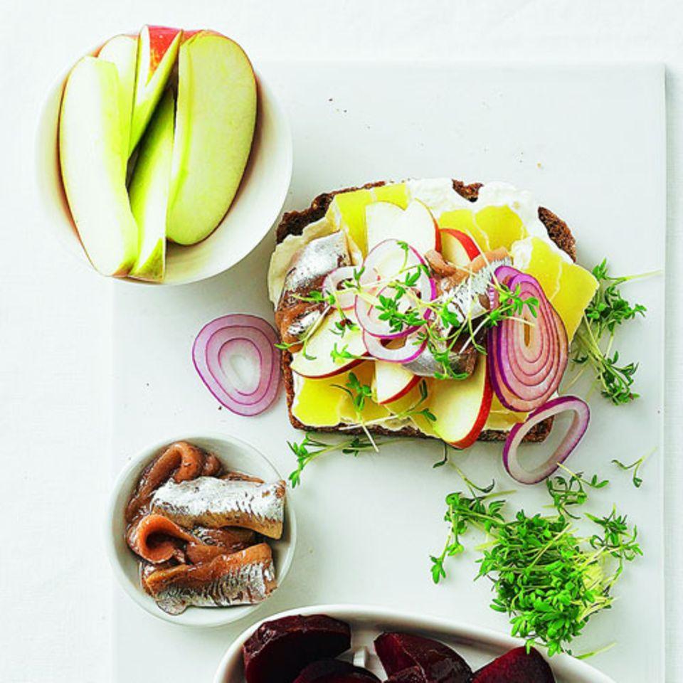 Ein opulentes Abendessen: Käsebrot mit Radieschen und Zwiebeln, dazu Appetitsild, rote Bete und Apfel. Wer rote Bete nicht mag, nimmt anderes Gemüse, etwa Paprikaschote, Möhre oder Tomaten.Zum Rezept: Smörrebröd mit Handkäse und Appetitsild