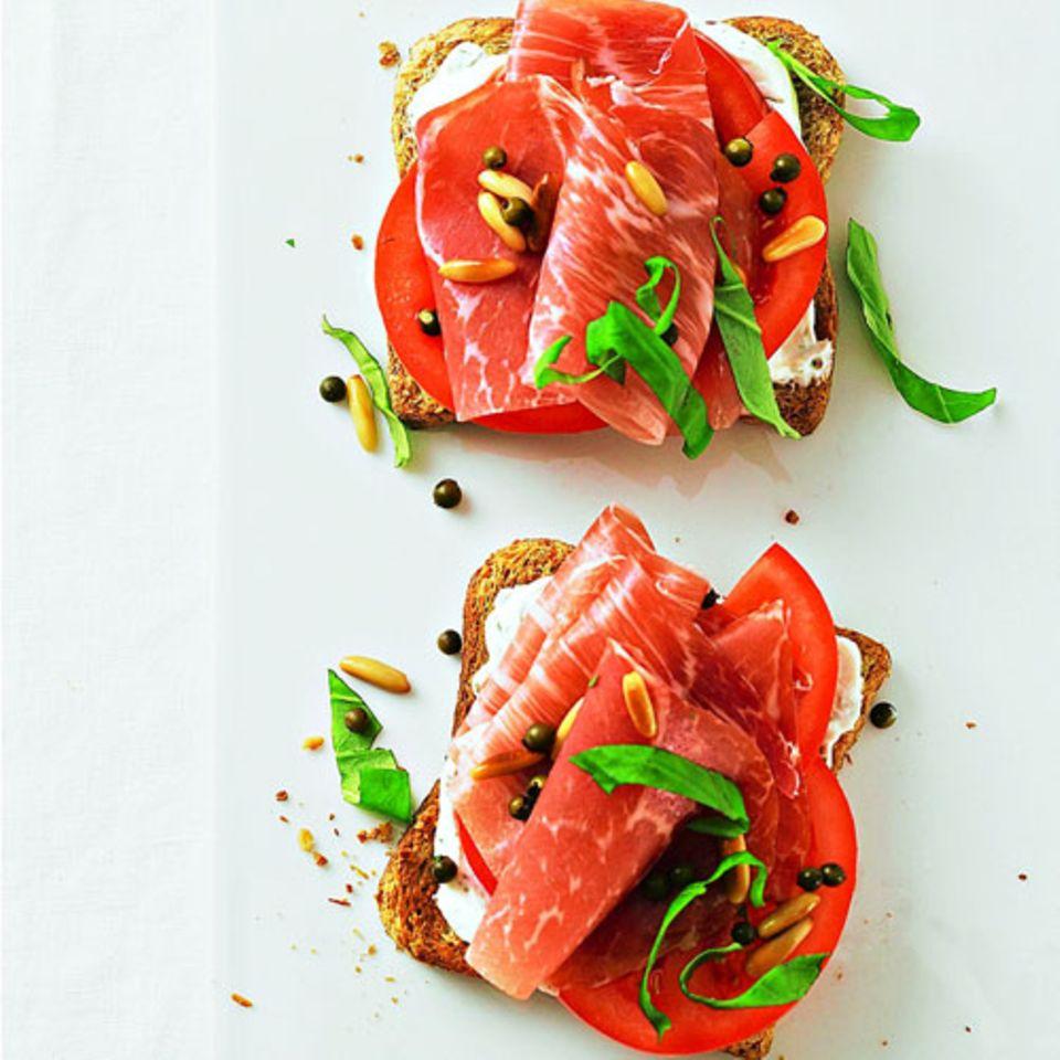 Wieder kommt Frischkäse zum Einsatz. Er bietet sich für Low-Carb-Brote an, denn er enthält Wasser, und das verdünnt quasi die Kalorien. Hier werden Magerquark und Ziegenfrischkäse mit Senf und Kräutern verrührt und auf ein Toastbrot gestrichen. Obendrauf: Tomate, Parmaschinken, grüner Pfeffer, Pinienkerne und Basilikum. Köstlich! Zum Rezept: Parmaschinken-Schnitten