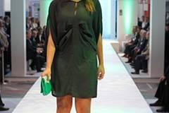 Esther trägt ein kurzes, dunkelgrünes Kleid von Very by Vero Moda, eine knallgrüne Tasche von Abro und Plateau-Sandalen von Buffalo.