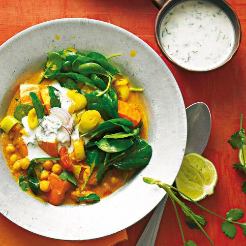 Indien grüßt süß-scharf-sauer: Gemüse und Kichererbsen in Curry-Kokos-Soße mit einem Klecks Raita, fein gewürztem Joghurt. Rezept: Kürbis-Spinat-Stew mit Raita