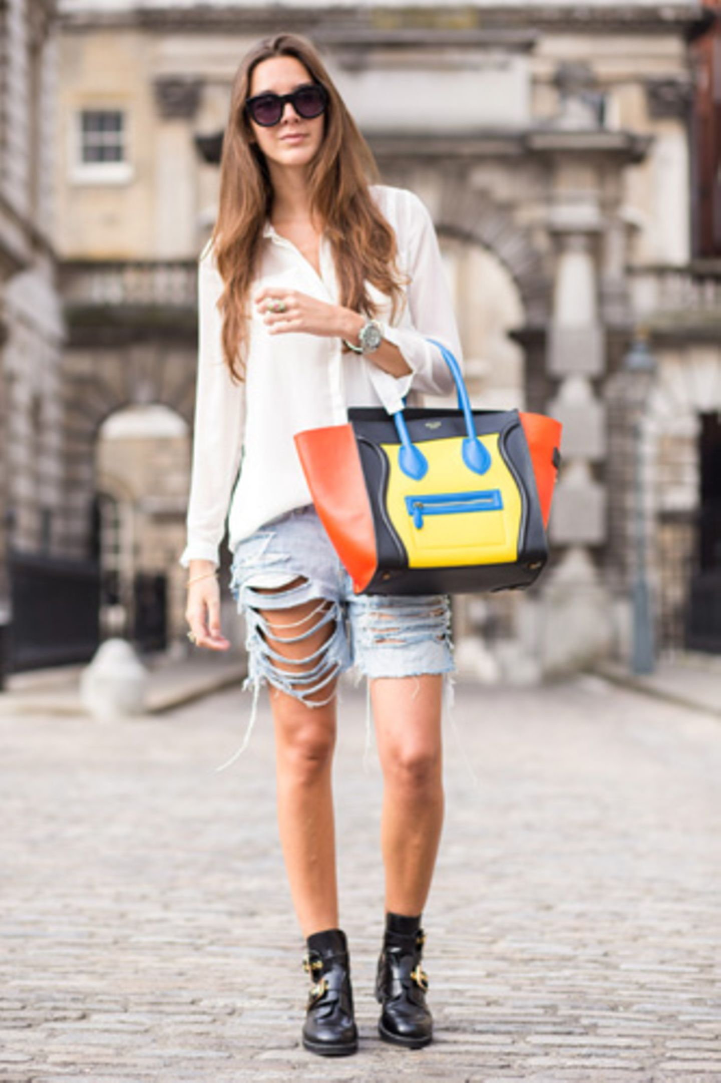 Ja, die Céline Luggage Bag gibt es auch in bunt - und die sieht zu schlichtem weißen Hemd und kunstvoll zerstörter Jeans-Shorts gar nicht mal so schlecht aus.