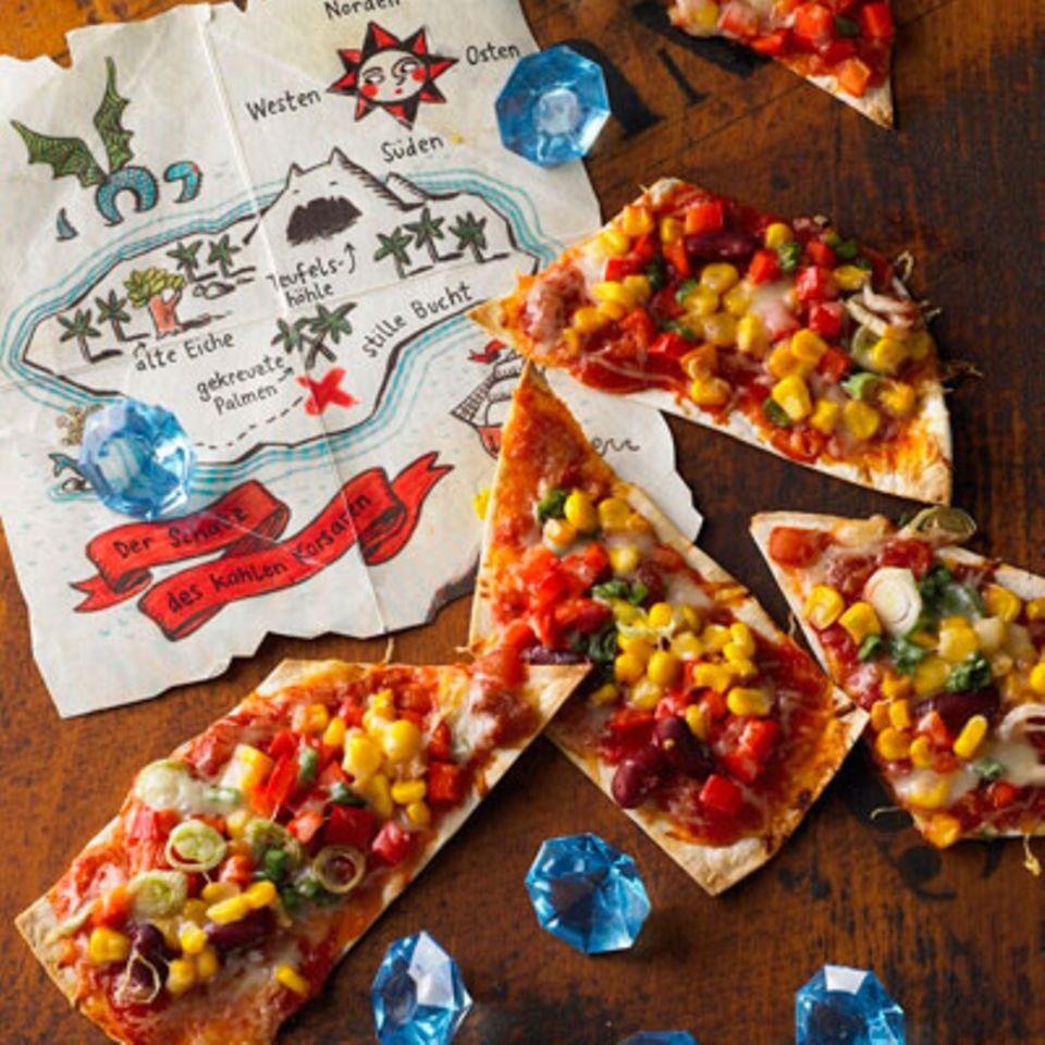 """Auf dieser kunterbunten Pizza ist für alle kleinen Entdecker was dabei - und auf diese Weise essen sie sogar das Gemüse gern mit. Piraten, die nicht lang still sitzen können, essen die Schatzkarte einfach aus der Hand. Zum Rezept: Pizza """"Schatzkarte"""""""