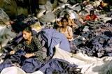 Textilarbeiterinnen zerschneiden Pullover, Jacken und Mäntel mit Gemüsemessern. Etiketten, auf denen die Namen teurer Labels und Produktinformationen stehen, werden für wertlos befunden und abgeschnitten. © Tim Mitchell, 2005