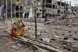 Vor den Trümmern der eingestürzten Fabrik wartet eine Mutter im Juli 2013 immer noch auf die Rückkehr ihrer Tochter Rina (18). © Taslima Akhter