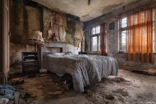 """Zeitzeugen: Auf verlassene Häuser stößt man eher zufällig. Es sei denn, man heißt Ransom Riggs und macht sich gezielt auf die Suche. Der Autor, der unter anderem den Roman """"Die Stadt der besonderen Kinder"""" (Originaltitel: """"'Miss Peregrines Home For Peculiar Children"""") geschrieben hat, ist durch Europa gereist, um Häuser zu finden, wie er sie in seinem Roman beschreibt. Die Häuser, die er fand, waren aber weniger gruselig. """"Einige dieser Häuser - leerstehend seit Jahrzehnten - waren vollständig unberührt. Wenn die dicken Staubschichten nicht gewesen wären, hätte es so ausgesehen, als wären sie noch bewohnt"""", sagte er dem """"Globe"""". Über seinen Verlag kontaktierte Riggs den Fotografen Martino Zegwaard, der leerstehende Gebäude fotografiert hatte. Zegwaard zur """"Huffington Post"""": """"Ich wurde von Ransom kontaktiert, nachdem Riggs eine Fotografie von mir gefunden hatte, die genau so aussah, wie er sich das Haus aus 'Miss Peregrines Home For Peculiar Children' vorgestellt hatte"""". Gemeinsam machten sich die beiden auf eine Reise durch Europa, um verlassene Gebäude aufzuspüren und zu fotografieren. Auf dem Bild oben sehen wir ein Haus in Belgien. """"Es ist schwer zu glauben, dass auf beiden Seiten des Hauses Menschen leben. Das kann doch nicht gesund sein für die Nachbarn. Da ist Schimmel in den Wänden und auf den Böden und das Erdgeschoss ist mit Müll bedeckt"""", schreibt Zegwaard."""
