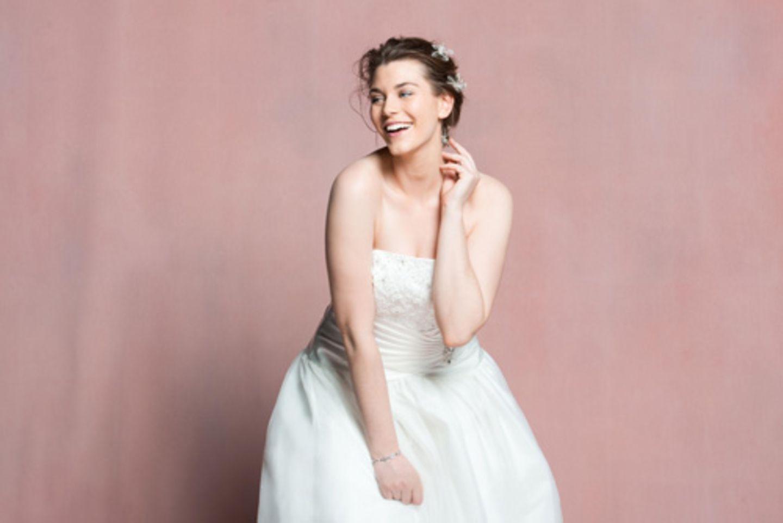 Der Online-Shop Navabi ist auf Premium-Mode ab Größe 42 spezialisiert – und hat jetzt, ganz neu, auch Brautmode im Sortiment. Das sind gute Neuigkeiten für werdende Bräute mit Kurven, denn gerade bei größeren Konfektionsgrößen ist es wichtig, dass ein Kleid nicht nur schöne Stoffe und Verzierungen zu bieten hat, sondern auch so geschneidert ist, dass es richtig sitzt und den Körper gut in Szene setzt. Die Brautmodenkollektion bei Navabi wurde vom britischen Label Linzi Jay entworfen – und umfasst Brautkleider von Größe 42 bis 54. Insgesamt gibt es zehn verschiedene Hochzeitskleider, wobei das Sortiment von klassischen Modellen aus Satin mit Perlen-Korsetts über extravagante Kleider mit Schleppen bis hin zu komplett aus zarter Organza-Spitze gefertigten Roben reicht. Die Preise der Brautkleider reichen von 699 bis 1299 Euro. Hier zu sehen: Bandeau-Brautkleid mit Tüllrock, mit verzierter Taillenraffung und Schnürung im Rücken, circa 900 Euro.