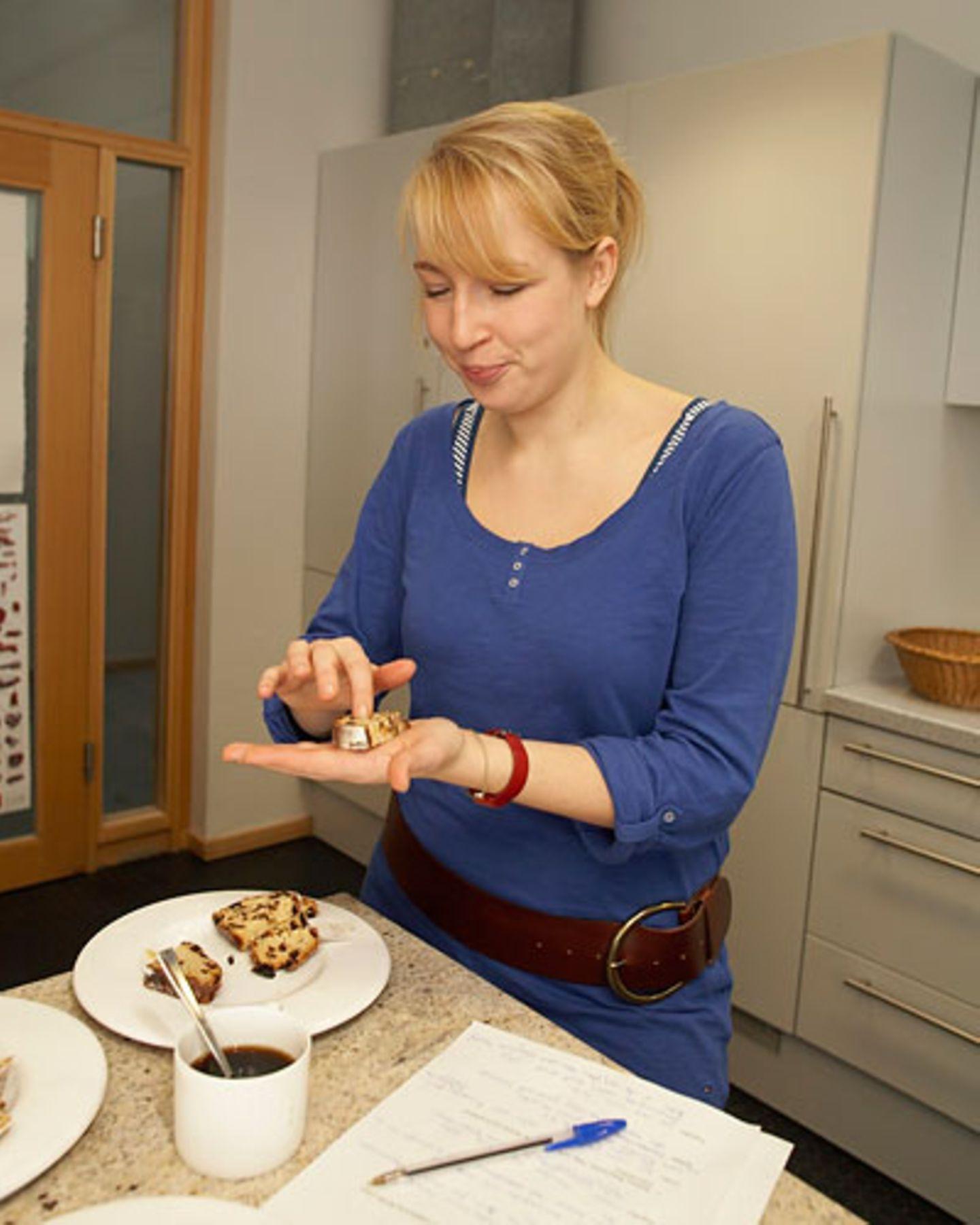 Sina drückt prüfend mit dem Finger in eine Scheibe Stollen - ist die Krume schön locker gebacken? Das Blatt für die Notizen liegt griffbereit neben dem Teller.