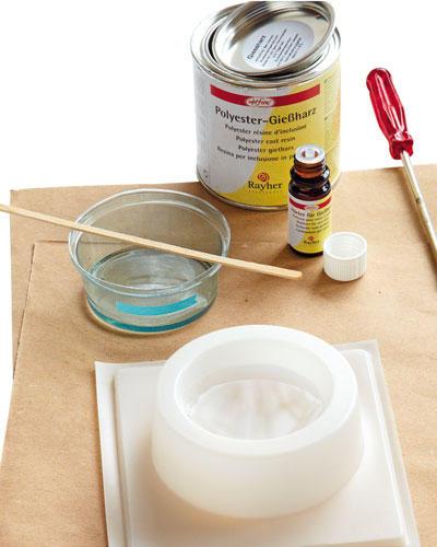 Bastelideen: Es wird in zwei Schichten gegossen, damit das Objekt beim Aushärten nicht reißt. Erst 50 ml Wasser abmessen, in den Deckel der Gießharzdose füllen und mit Tape oder wasserfestem Stift die Füllhöhe markieren. Wasser ausgießen, Becher abtrocknen. 50 ml Gießharz in den Becher gießen, dann zwölf Tropfen Härter gut unterrühren. Die Masse in die Gießform, die auf einer Unterlage steht, füllen. 30-90 Minuten anziehen lassen (je nach Raumtemperatur).