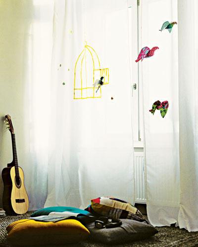 """Das brauchen Sie für den Vorhang: Vorhang """"Vivan"""" (Ikea); goldenen Stoffmalstift; schwarzen Edding; Zeitung So geht's: Einen offenen Vogelkäfig mit Edding auf Zeitungspapier malen. Den Vorhang darauflegen und mit dem goldenen Stoffmalstift den durchscheinenden Käfig nachzeichnen. Das brauchen Sie für die Stoffvögel: farbig ausgedrucktes Schnittmuster, pro Vogel 30 x 35 cm Stoff; Bleistift; Schere; Füllwatte; Garn; Nähmaschine So geht's: Vorlage auf Stoff übertragen, ausschneiden. Bauch und Körper je rechts auf rechts entlang der Nahtlinie aneinandersteppen, dafür die pinken Markierungen aufeinanderlegen. Flügelteile rechts auf rechts aneinandersteppen, wenden. Körper mit Watte ausstopfen. Schwanzende zunähen, Ziernähte einnähen. Flügel bügeln, mit Ziernähten versehen, per Hand zunähen, an den Körper heften. """"Entflogene"""" Vögel mit Fäden an der Decke aufhängen."""