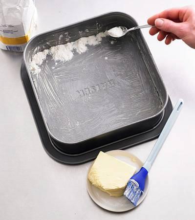 Backschule: Eine quadratische Springform (23 cm Seitenlänge) gut mit Butter ausfetten und an eine Seite einen Streifen Mehl streuen. Die Form leicht schräg halten, so dass der Mehlstreifen oben ist.