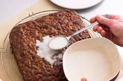 Das fertig gebackene Früchtebrot kurz abkühlen lassen, aus der Form lösen und auf ein Kuchengitter legen. Für die Deko Puderzucker und Sherry zu einem glatten Guss verrühren und auf dem Kuchen verteilen.