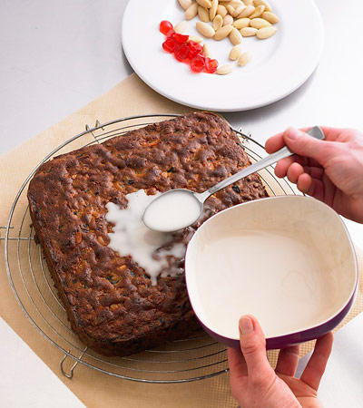 Backschule: Das fertig gebackene Früchtebrot kurz abkühlen lassen, aus der Form lösen und auf ein Kuchengitter legen. Für die Deko Puderzucker und Sherry zu einem glatten Guss verrühren und auf dem Kuchen verteilen.
