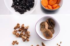 Für den Teig: Die Kirschen halbieren oder vierteln. Feigen, Aprikosen und Backpflaumen in kleine Würfel schneiden. Die getrockneten Beeren der Beerenmischung grob hacken. Mandeln und Walnusskerne ebenfalls grob hacken.