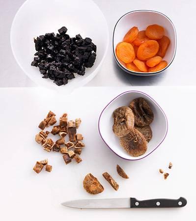 Backschule: Für den Teig: Die Kirschen halbieren oder vierteln. Feigen, Aprikosen und Backpflaumen in kleine Würfel schneiden. Die getrockneten Beeren der Beerenmischung grob hacken. Mandeln und Walnusskerne ebenfalls grob hacken.