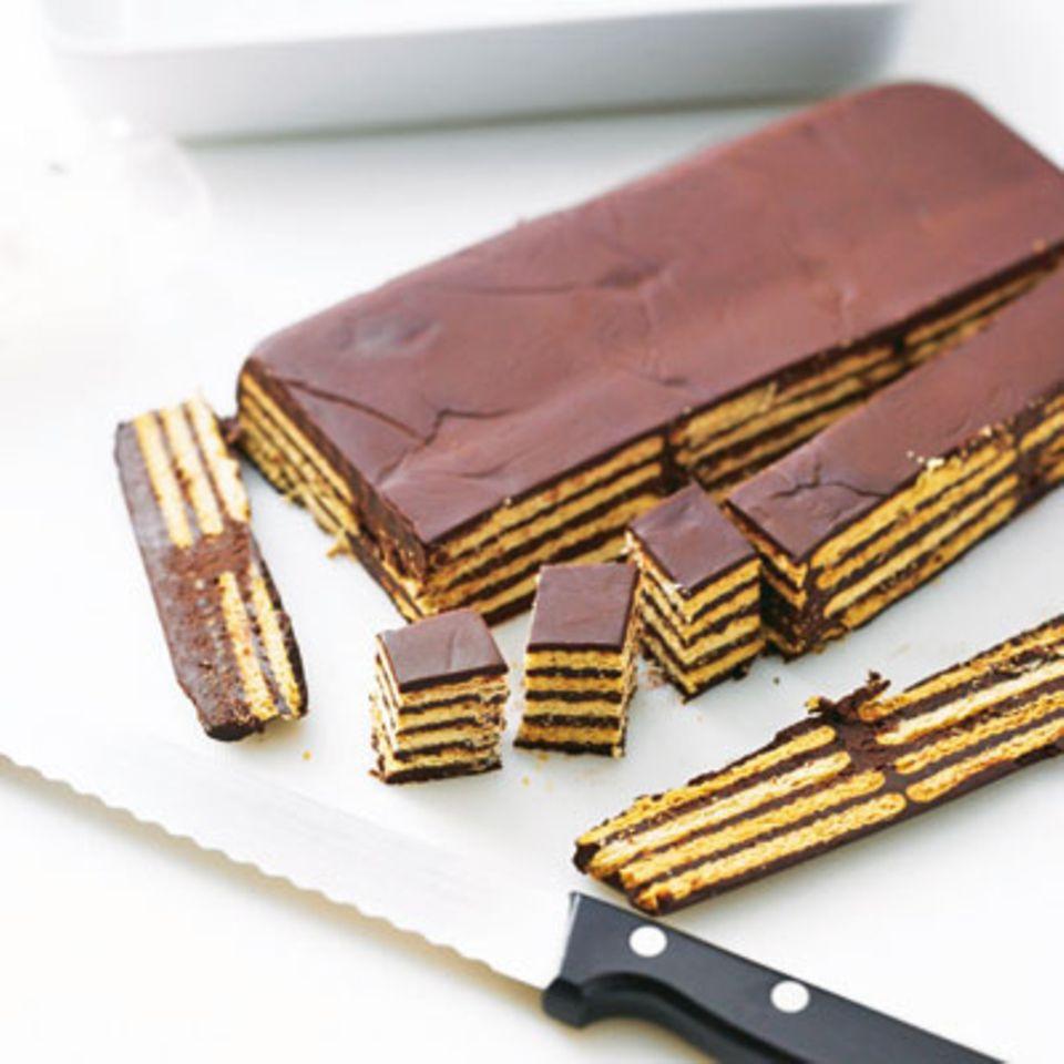 Stürzen und die Ränder gerade schneiden. Mit einem Sägemesser in 2 cm große Quadrate schneiden und je eine Kaffeebohne oben in die Schokolade drücken.
