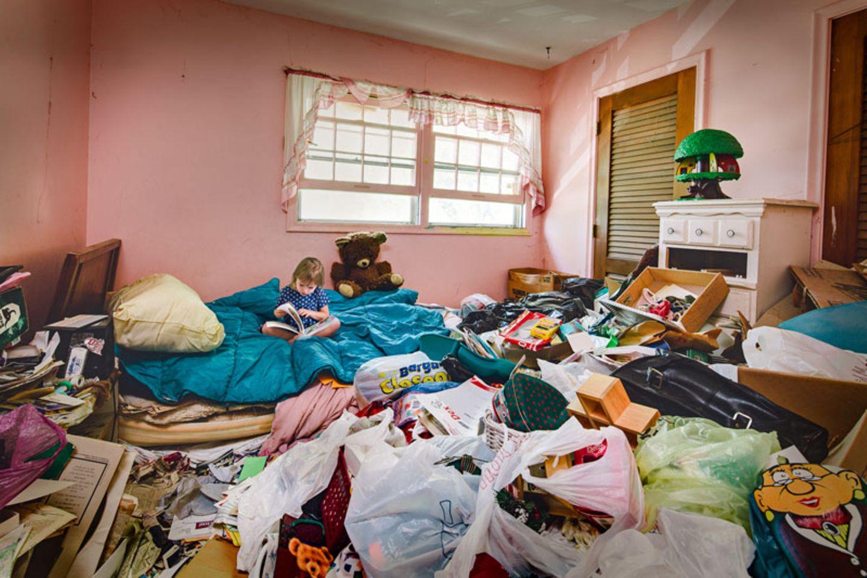 """""""Behind the Door"""" hat Fotograf Geoff Johnson seine Fotoreihe genannt. Hinter der Tür, der Tür seines Zuhauses, hat er sich als Junge regelmäßig versteckt, wenn es klingelte. Er stand ganz still und wartete, bis der Besuch wieder wegging. Dann atmete er auf. Erleichtert darüber, dass niemand gesehen hat, wie es im Inneren seines Zuhauses aussah. Denn in seinem Zuhause herrschte das Chaos. Geoffs Mutter litt am Messie-Syndrom. Menschen mit dieser psychischen Störung sind nicht in der Lage, Dinge wegzuwerfen und ihr Zuhause in Ordnung zu halten. In Deutschland sind Schätzungen zufolge rund 1,8 Millionen Menschen davon betroffen. Seine gesamte Kindheit verbrachte Geoff in einem Haus, das komplett verwahrlost war. Erst 20 Jahre nach seinem Auszug kehrte er dahin zurück. Die Mutter war inzwischen gestorben. An dem Zustand im Haus hatte sich nichts geändert. Geoff und seine Schwester Jennifer beschlossen, den Ort ihrer Kindheit in einer Fotoreihe zu dokumentieren. Auch, um das Erlebte endlich zu verarbeiten."""