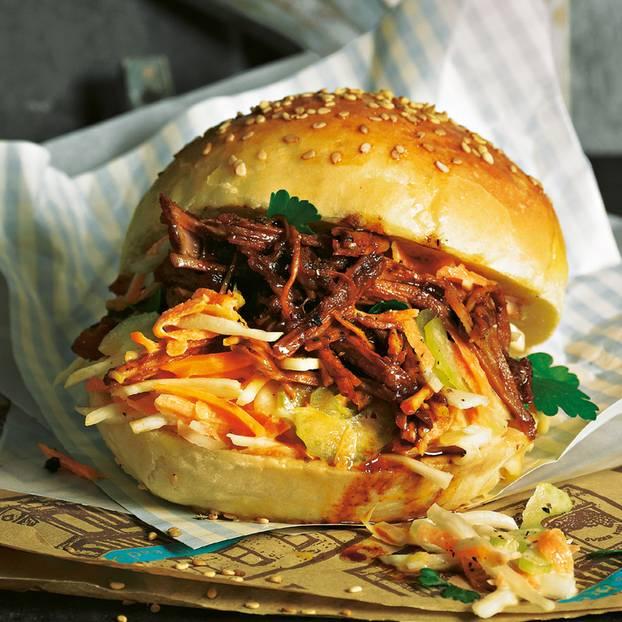 """Bevor das Schweinefleisch, ins Brötchen kommt, wird es langsam so zart gegart, dass man es in Streifen vom Knochen lösen kann. Zum Rezept: """"Pulled Pork""""- Burger Zum Rezept: Coleslaw"""