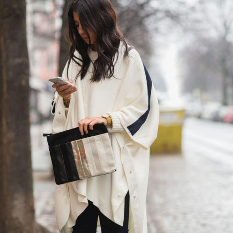 Seit Montag präsentieren deutsche Designer ihre Kollektionen für den kommenden Winter im Rahmen der Mercedes Benz Fashion Week Berlin. Wenn auch keine internationale Stars vor Ort waren - was nicht weiter schlimm ist - so gaben sich zumindest die internationalen Modeblogger die Ehre und beglücken uns mit herrlichen Outfitkombinationen. Der Januar ist natürlich immer eine kleine Herausforderung, bei eiskalten Temperaturen kann man außer einem schicken Mantel nicht viel zeigen, ohne Erfrierungen an den Extremitäten zu riskieren. Bloggerin Kayla Seah von Not Your Standard löst das Outfit-Dilemma mit Hilfe eines kuscheligen Pullis plus passendem Cape. Die farblich passende XL-Clutch und die goldene Uhr runden das Outfit ab.