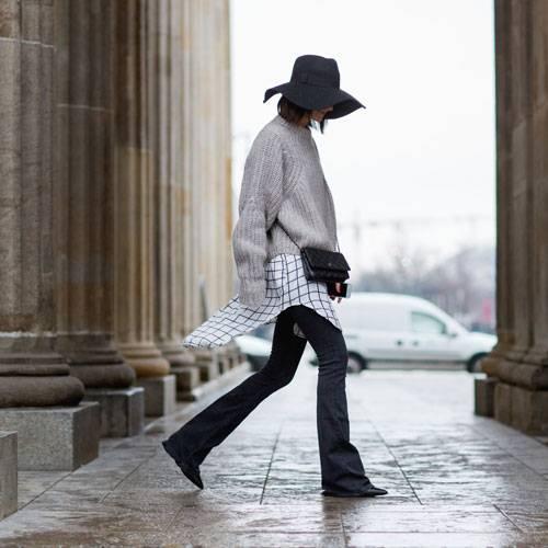 Streetstyle: Golestaneh kombiniert zum grauen Pulli einen Hingucker-Hut, ein schwarz-weiß kariertes Hemd und Jeans mit leichtem Schlag - ohne die geht gerade anscheinend nichts. Finden wir auch.