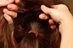 Die Haare am Oberkopf leicht antoupieren, mit Haarspray besprühen. Die aufgebauschten Partien mit den Fingern ein wenig glätten, dann in zwei Stränge einteilen.