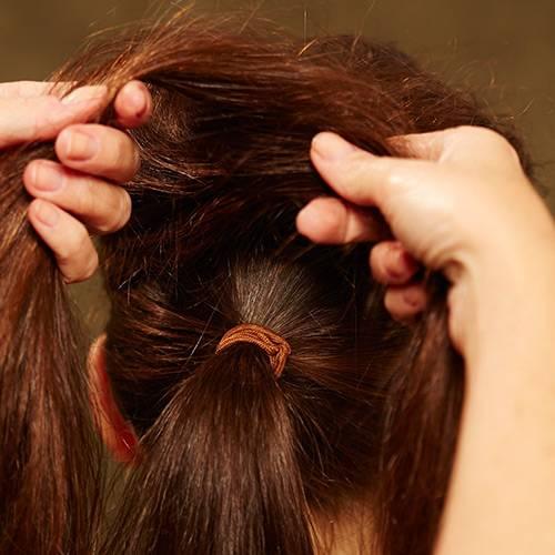 Frisuren: Die Haare am Oberkopf leicht antoupieren, mit Haarspray besprühen. Die aufgebauschten Partien mit den Fingern ein wenig glätten, dann in zwei Stränge einteilen.